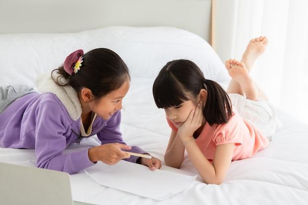 Asian little girl czytanie książki na łóżku z komputera notebook razem