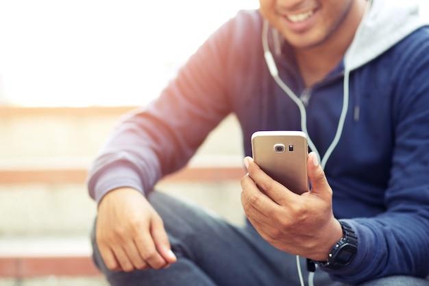 Asian mężczyzna jogger słuchanie muzyki w słuchawkach po treningu przy dobrej pogodzie.