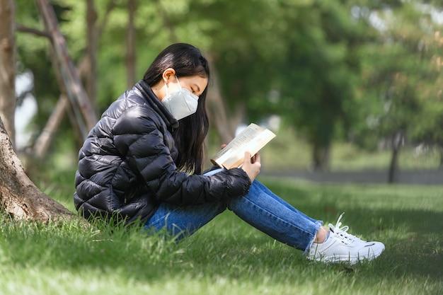 Asian młoda dziewczyna zamierza cieszyć się czytaniem książki do przygotowania egzaminu końcowego, siedząc pod drzewami w parku na świeżym powietrzu w czasie nauki w letni dzień. koncepcja edukacji uczenia się studiów.
