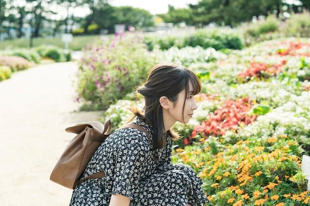 Asian młoda kobieta na spacer w kwiatowym polu