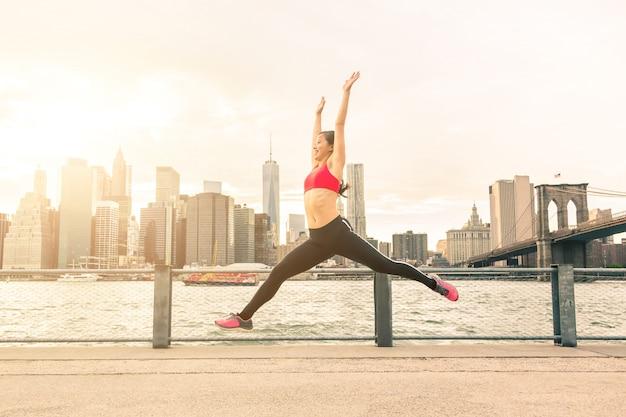 Asian młoda kobieta skoki z panoramą nowego jorku