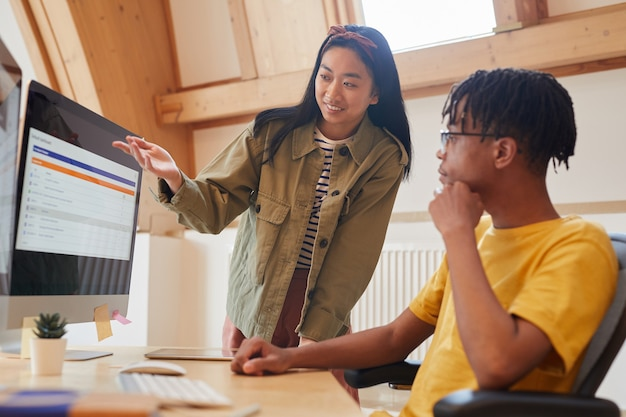 Asian młoda kobieta, wskazując na monitorze komputera i omawiając z kolegą nowe oprogramowanie podczas pracy w biurze