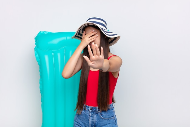 Asian młoda kobieta zakrywająca twarz ręką i kładąc drugą rękę na białym tle