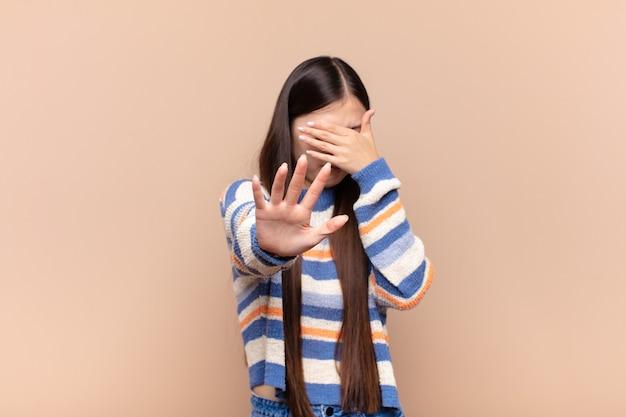 Asian młoda kobieta zakrywająca twarz ręką i kładąc drugą rękę z przodu, aby zatrzymać gest