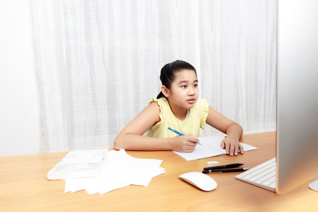 Asian młoda mała dziewczynka za pomocą ołówka do samodzielnego odrabiania lekcji
