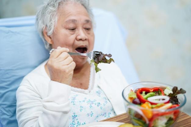 Asian pacjent starszy kobieta jedzenie śniadanie w szpitalu.