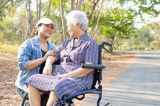 Asian pacjent starszy kobieta na wózku inwalidzkim w parku.