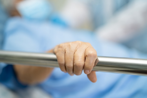 Asian pacjent starszy kobieta położyć się uchwyt łóżka poręczy.