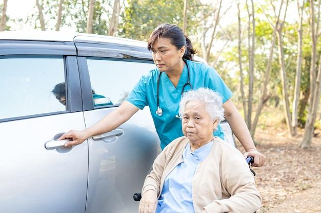 Asian pacjent starszy kobieta siedzi na wózku inwalidzkim przygotować dostać się do samochodu.