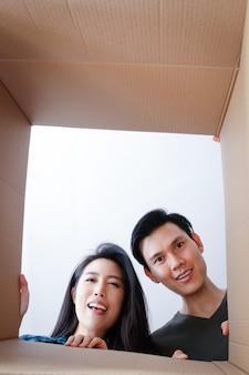 Asian para przeprowadzka do nowego domu otwórz duży brązowy karton. wesoły uśmiech. koncepcja rodziny para przeniosła się do nowego domu, aby zbudować rodzinę.