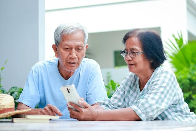 Asian para starszych szczęśliwego życia w domu siedząc w ogrodzie, trzymając smartfon, rozmawiając online z dzieckiem. koncepcja rodziny, opieka zdrowotna dla osób starszych w wieku emerytalnym