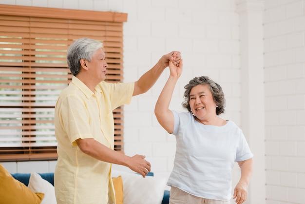 Asian para starszych tańczących razem podczas słuchania muzyki w salonie w domu, słodka para cieszyć się chwilą miłości podczas zabawy, gdy jest zrelaksowana w domu.