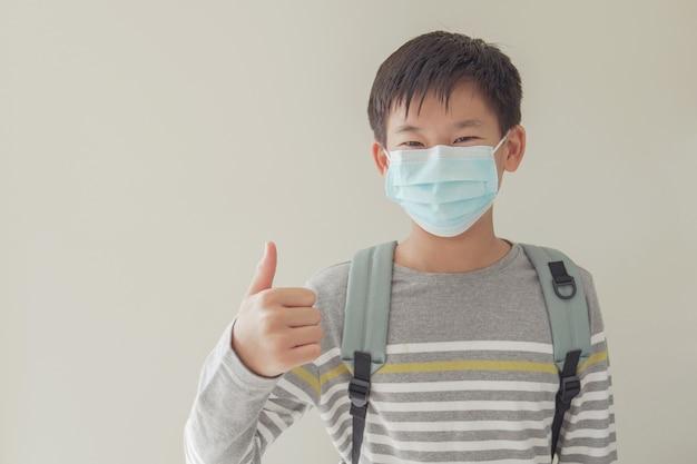 Asian preteen noszący maskę i dając kciuk do góry