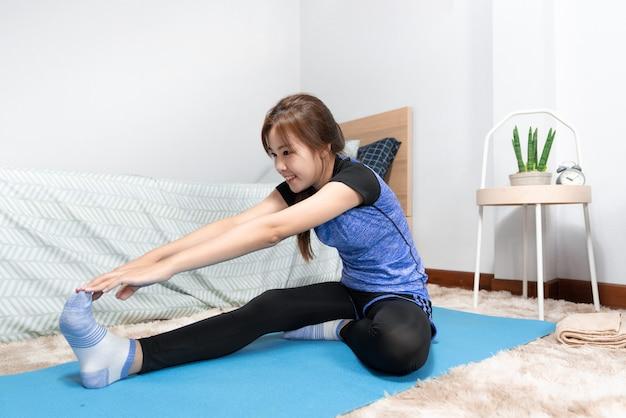 Asian robi fitness w domu i jogi na macie fitness robi ćwiczenia