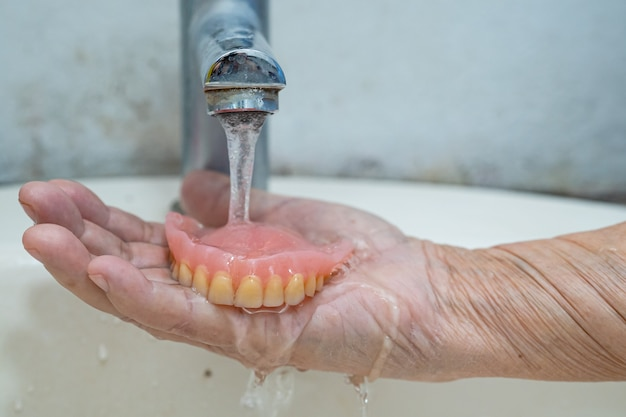 Asian senior lub starsza starsza kobieta pacjenta trzyma protezę częściową zębów zastępczych.