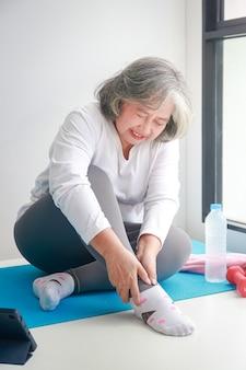 Asian starsza kobieta ćwiczenia w domu ranny na prawej kostce. jest dużo bólu. koncepcja opieki zdrowotnej dla seniorów.