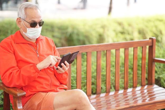 Asian stary starszy mężczyzna starszy mężczyzna noszenie maski na twarz za pomocą telefonu komórkowego inteligentny telefon komórkowy odkryty