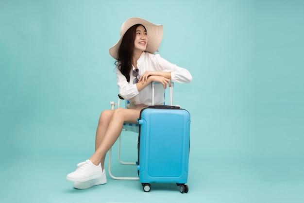 Asian szczęśliwa kobieta siedzi na krześle z walizką