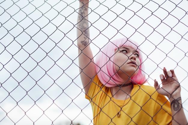 Asian teen girl w stylowy strój chwytając netto ogrodzenie