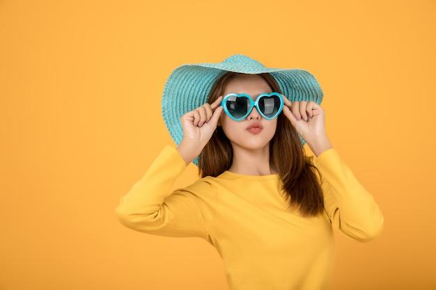 Asian woman dress up concept wakacje z żółtą koszulą okulary i kapelusze są niebieskie i sprawiają, że twarze są bardzo szczęśliwe.