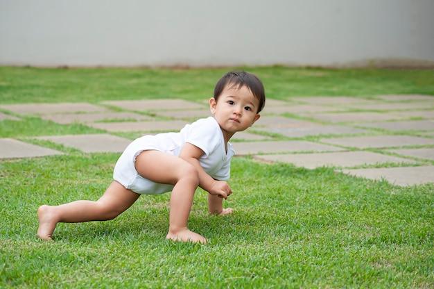 Asian wyglądająca 1-letnia dziewczyna gra na trawie gospodarstwa. selektywna ostrość. skopiuj miejsce
