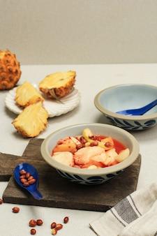 Asinan buah bogor, marynata owocowa z pokrojonych w plasterki świeżych owoców tropikalnych na słodkiej, kwaśnej i pikantnej czerwonej zupie. posypane smażonymi orzeszkami ziemnymi słynne podczas ramadanu.