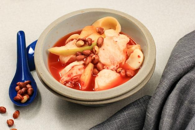 Asinan buah bogor (rujak buah), marynata owocowa z pokrojonych świeżych owoców tropikalnych na słodkiej, kwaśnej i pikantnej czerwonej zupie. posypane smażonymi orzeszkami ziemnymi słynne podczas ramadanu.
