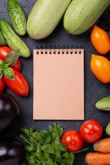Asortowani surowi organicznie warzywa i rzemiosło notatnik na zmroku drylują tło