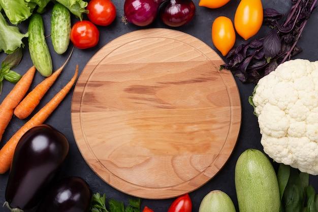 Asortowani surowi organicznie warzywa i tnąca deska na zmroku drylują tło
