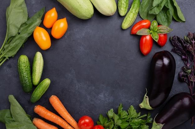 Asortowani surowi organicznie warzywa na zmroku drylują tło