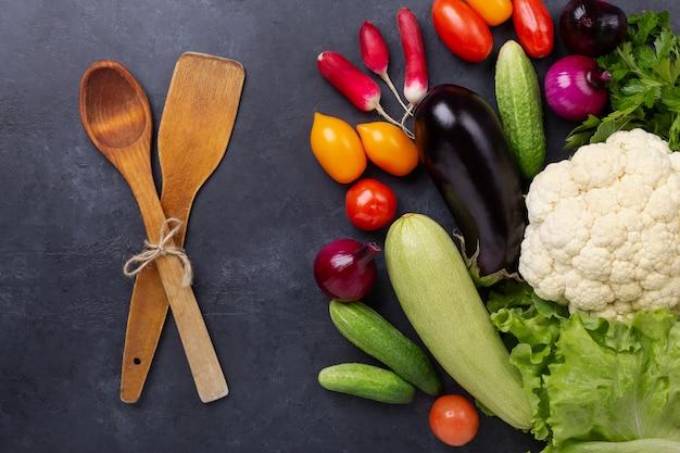 Asortowani surowi organicznie warzywa na zmroku kamieniu