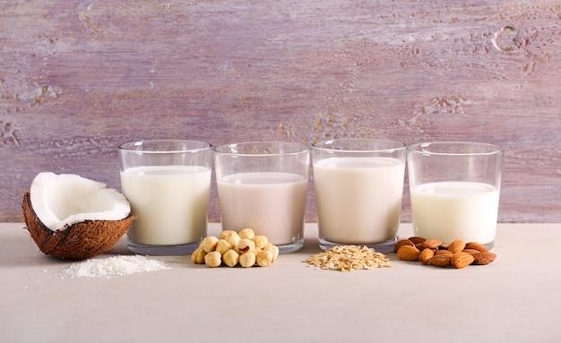 Asortyment bezmlecznych zamienników mleka: mleko kokosowe, orzechowe, owsiane i migdałowe