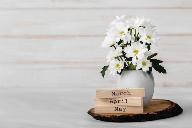 Asortyment białych kwiatów w białym wazonie z miejscem na kopię