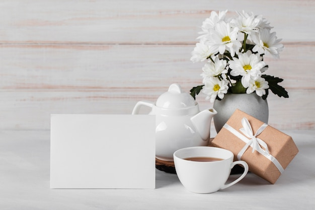 Asortyment białych kwiatów z pustą kartą i herbatą