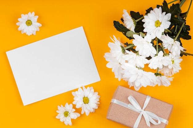 Asortyment białych kwiatów z pustą kartą i zapakowanym prezentem