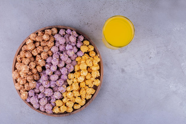 Asortyment cukierków popcorn ze szklanką napoju na marmurowym tle. zdjęcie wysokiej jakości