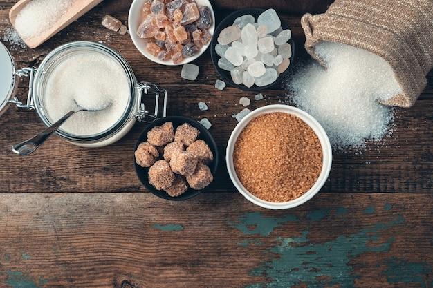 Asortyment cukru różnych typów i odmian na drewnianym tle.