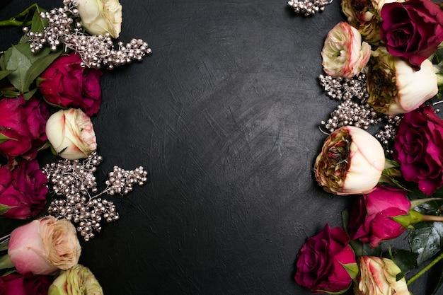 Asortyment czerwonych i różowych róż z dekoracją srebrnych koralików na ciemnym tle. piękny kwiatowy wzór. miłość i piękno. koncepcja copyspace