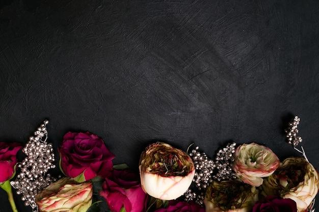 Asortyment czerwonych i różowych róż z dekoracją srebrnych koralików na ciemnym tle. piękny kwiatowy wzór. miłość i piękno. koncepcja wolnej przestrzeni