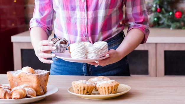 Asortyment deserów cukierniczych. kobiece hobby i styl życia. kobieta układa talerze ze świeżymi domowymi bezami, babeczkami, rogalikami i keksami.
