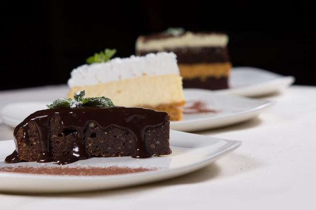 Asortyment deserów w piekarni lub restauracji z pojedynczymi plasterkami bogatej tarty czekoladowej, tortem i sernikiem podawanym na talerzach przy stole