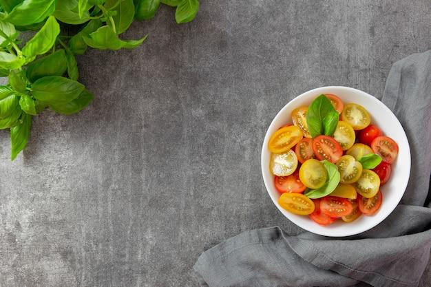 Asortyment dojrzałych wielobarwnych organicznych rolników pomidorów cherry z liśćmi bazylii w białej misce na ciemnym tle.
