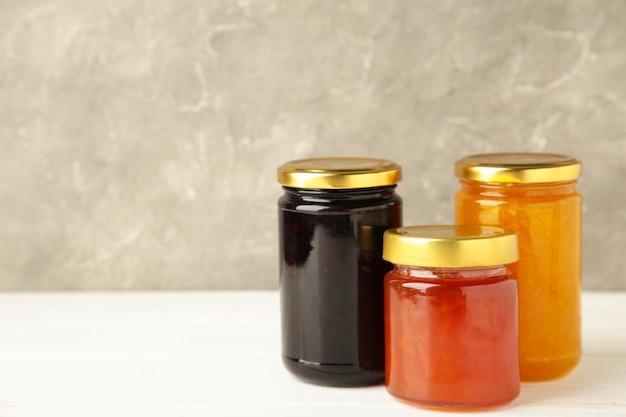 Asortyment dżemów, sezonowych świeżych jagód i owoców na białym tle.