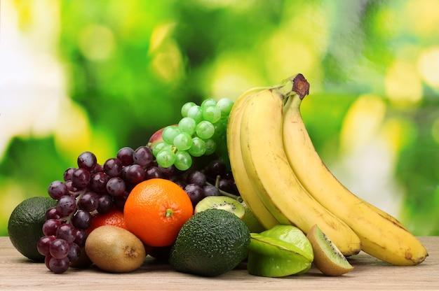 Asortyment egzotycznych owoców na drewnianym stole na zielonym tle