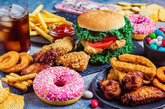 Asortyment fast food. koncepcja fast foodów. niezdrowa żywność dla serca, zębów, skóry, sylwetki.
