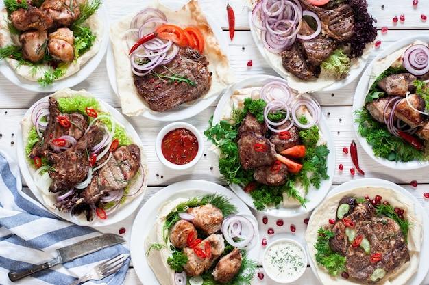Asortyment grillowanych dań mięsnych układanych na płasko. widok z góry na stół w restauracji z różnymi rodzajami grilla