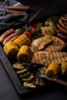 Asortyment grillowanych kiełbas, mięs i warzyw. piknikowa koncepcja grilla. ciemny styl