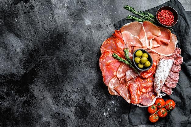 Asortyment hiszpańskiego wędlin. chorizo, fuet, lomo, jamon iberico, oliwki. czarne tło. widok z góry. skopiuj miejsce