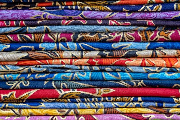 Asortyment kolorowych sarongów na sprzedaż na lokalnym rynku, wyspa bali, ubud, indonezja. ścieśniać