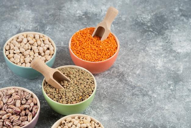 Asortyment kompozycji surowych suchych roślin strączkowych na marmurowej powierzchni stołu.
